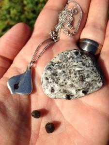 Två granater, en sten med granter i och mitt halsband med en granat från Abisko.